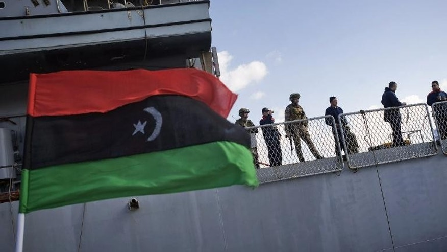 File picture shows an old Libyan national flag fluttering next to the Italian warship in the eastern Libya port of Benghazi on March 7, 2011