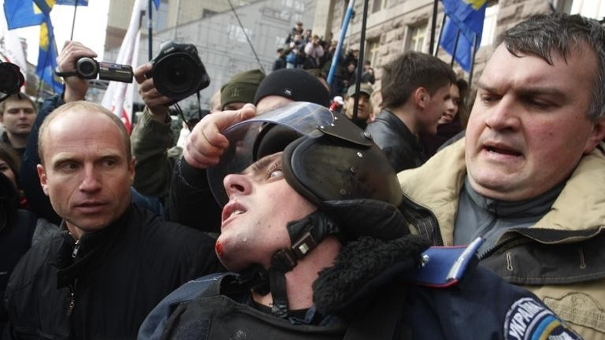 A Ukrainian opposition activist grabs the helmet of a riot policeman during clashes in Kiev, on October 2, 2013