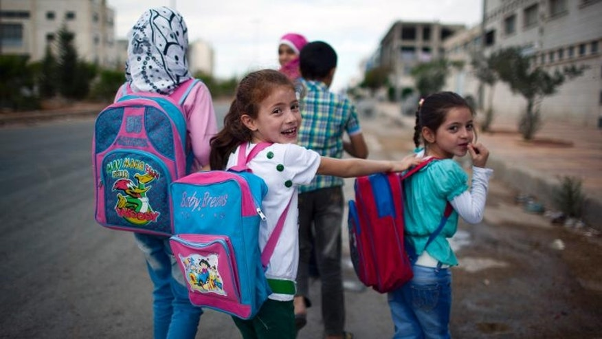 Syrian children head to school in the Sheikh Najjar district of the northern city of Aleppo, on September 23, 2013