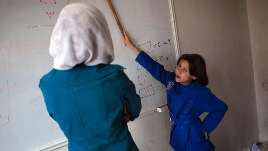 A Syrian student shows a word on a whiteboard during a class in the Masai Hanano district of Aleppo, on September 23, 2013