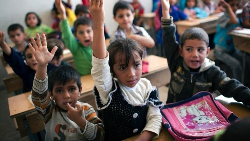 Syrian children attend a class at a school in the Masai Hanano district of the northern city of Aleppo, on September 23, 2013