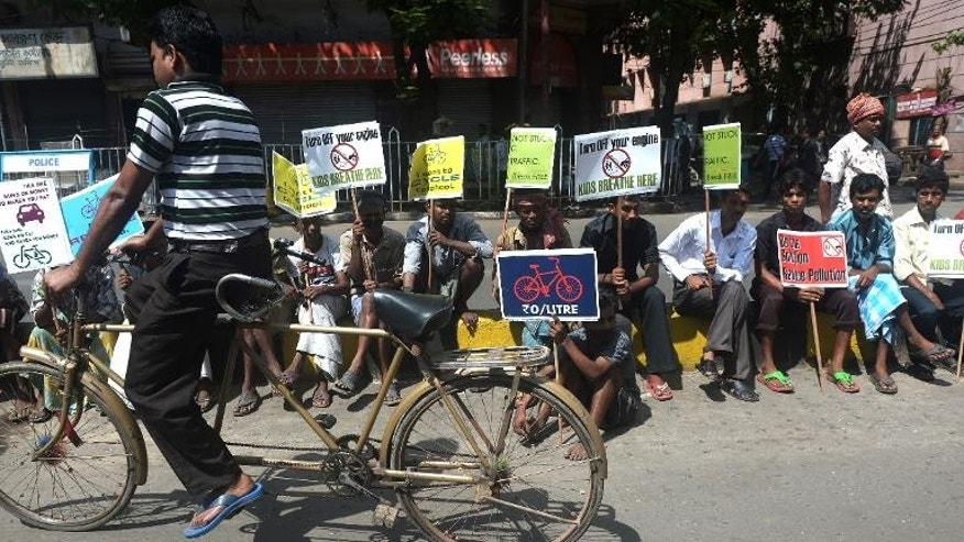 Indian rickshaw riders and cyclists sit with placards during a protest in Kolkata, on October 2, 2013