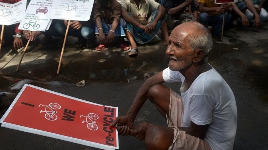 Indian rickshaw riders sit with placards during a protest in Kolkata, on October 2, 2013