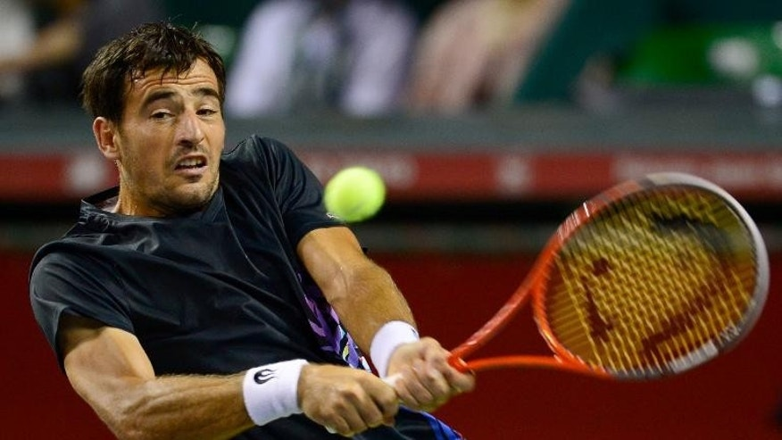 Ivan Dodig of Croatia hits a return against Jo-Wilfried Tsonga of France during their second round match at the Japan Open tennis tournament in Tokyo on October 2, 2013