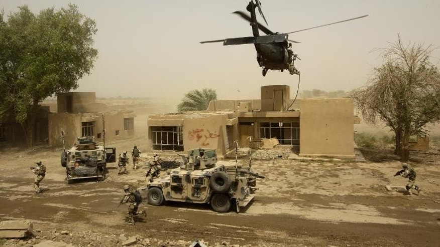 A helicopter hovers over Iraqi special anti-terror forces as they train during in Baghdad, on August 4, 2009