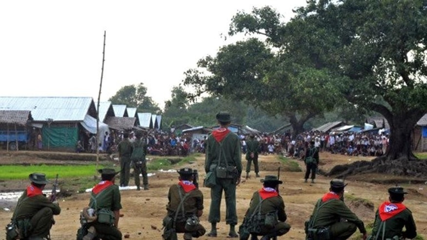 Myanmar security forces stand guard following unrest at an Internally Displaced People camp for Muslim Rohingyas near Sittwe town in Rakhine State on August 9, 2013