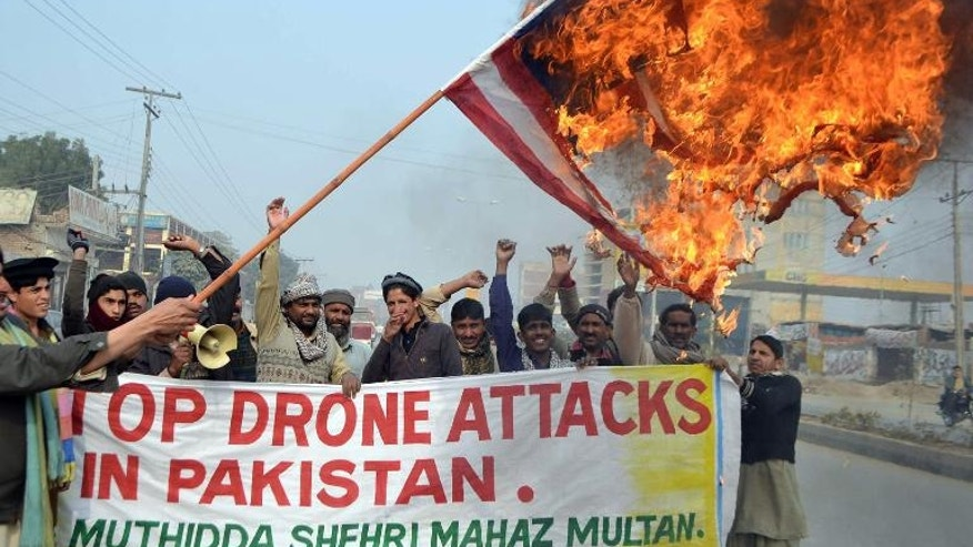 A Pakistani demonstrator holds a burning US flag during a protest in Multan against drone attacks in tribal areas, on January 8, 2013