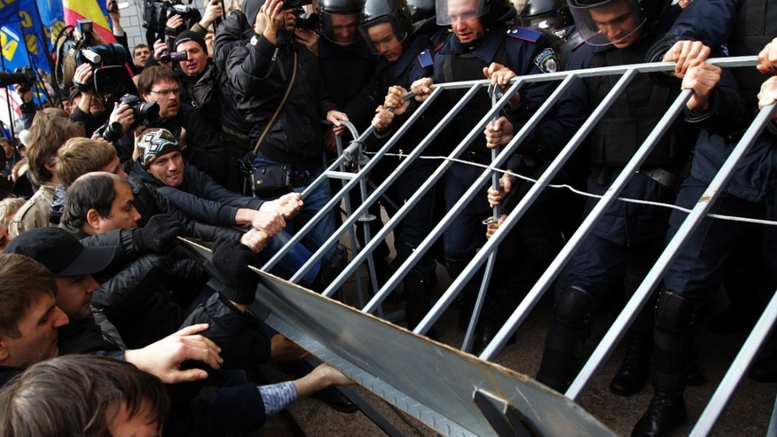 Opposition activists tussle with riot police, outside the Kiev city council building, during a protest rally demanding a re-election of the city council,  in Kiev, Ukraine, Wednesday, Oct. 2, 2013.  (AP Photo/Sergei Chuzavkov)