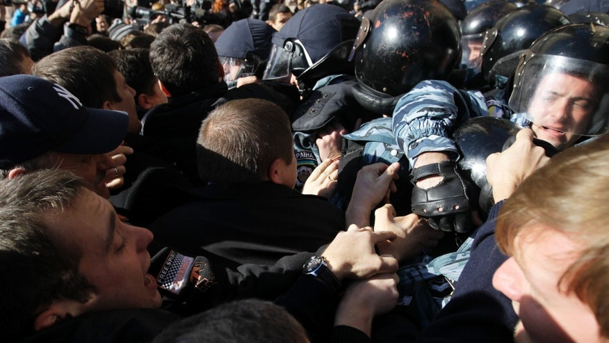 Opposition activists react with riot police, outside the Kiev city council building, during a protest rally demanding a re-election of the city council,  in Kiev, Ukraine, Wednesday, Oct. 2, 2013.  (AP Photo/Sergei Chuzavkov)
