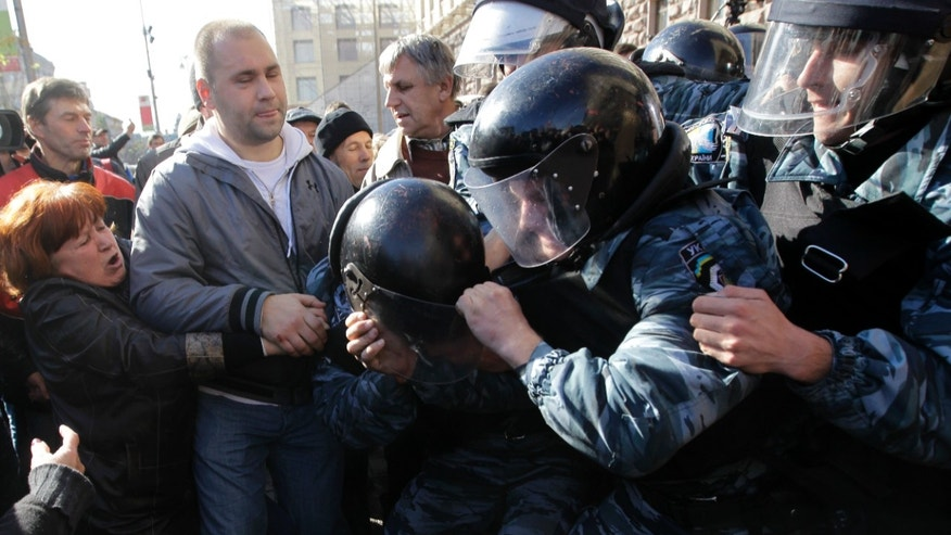 Ukraine riot police block opposition activists, outside the Kiev city council building, during a protest rally demanding a re-election of the city council,  in Kiev, Ukraine, Wednesday, Oct. 2, 2013.  (AP Photo/Sergei Chuzavkov)
