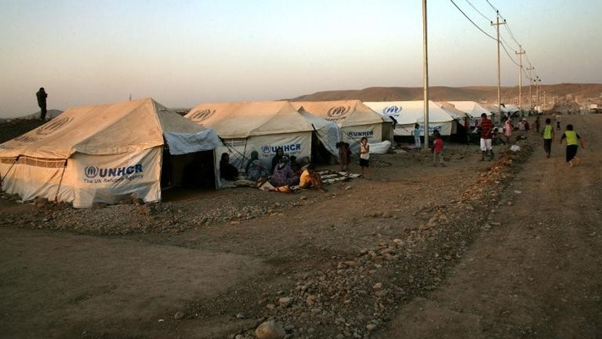 A file picture taken on August 27, 2013, shows Kurd refugees from Syria sitting outside tents provided by the UN High Commission for Refugees (UNHCR) at the Quru Gusik refugee camp in northern Iraq