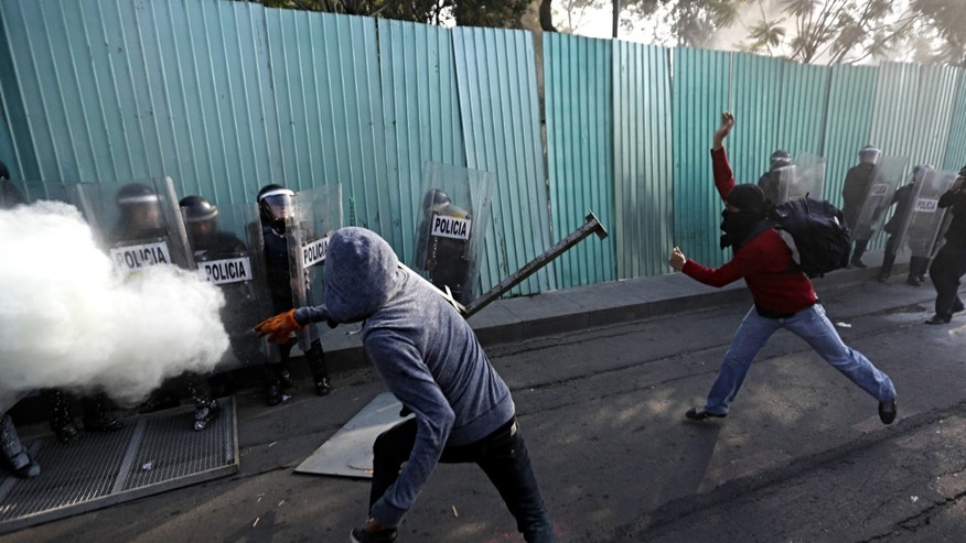 Masked protesters clash with riot police during a march marking the anniversary of the Tlatelolco massacre in Mexico City, Wednesday, Oct. 2, 2013. Mexico commemorated the 45th anniversary of the massacre of students holding an anti-government protest, killed by men with guns and soldiers ten days before the 1968 Summer Olympics celebrations in Mexico City. (AP Photo/Eduardo Verdugo)