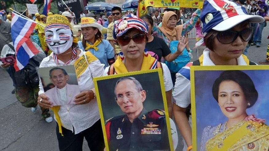 Anti-government protesters hold portraits of Thai King Bhumibol Adulyadej and Queen Sirikit during a demonstration in Bangkok, on August 18, 2013