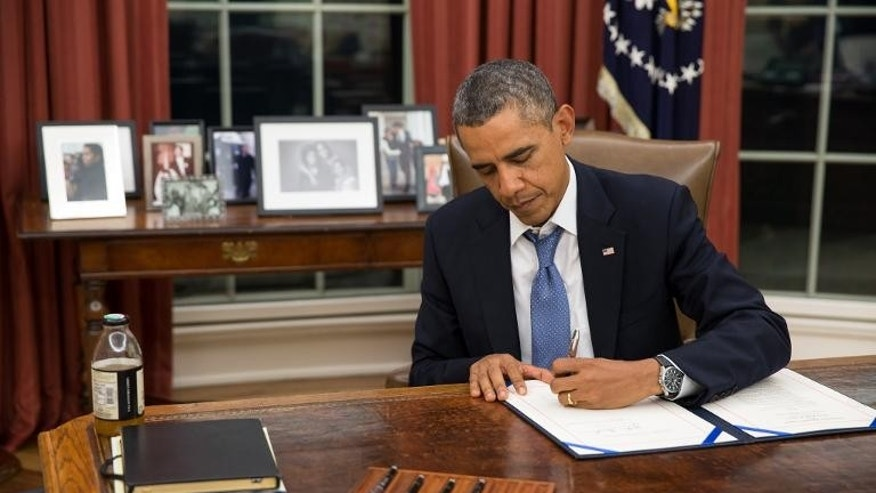 White House photo shows US President Barack Obama as he signs the Pay Our Military Act, which provides continuing appropriations for pay and allowances for the military, in the Oval Office, on September 30, 2013