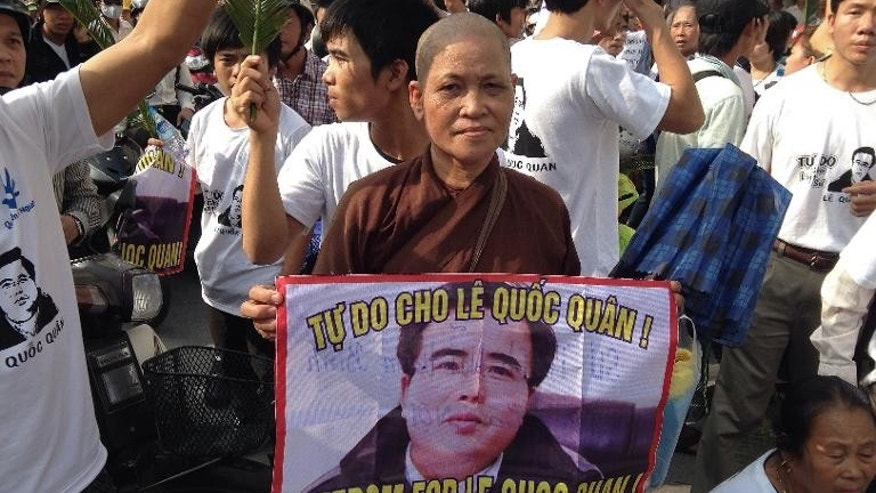 A Buddhist nun holds a picture of Vietnamese activist Le Quoc Quan as hundreds of protesters attempt to approach the People's Court in Hanoi, on October 2, 2013