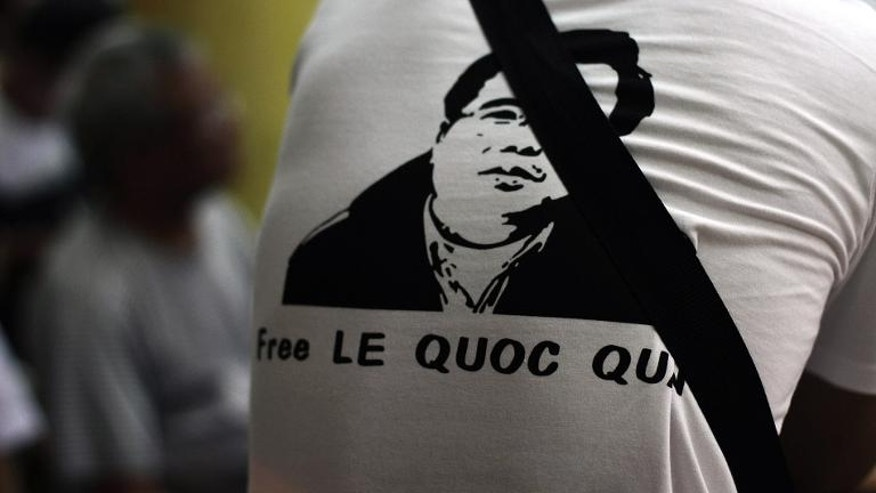 A protester wears a T-shirt with a portrait of democracy activist Le Quoc Quan, seen among worshipers during a mass at a catholic church in Hanoi, on July 7, 2013