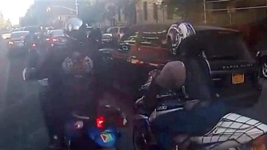 In this frame grab from video, motorcyclists ride alongside a sport utility vehicle, Sunday, Sept. 29, 2013, in New York.