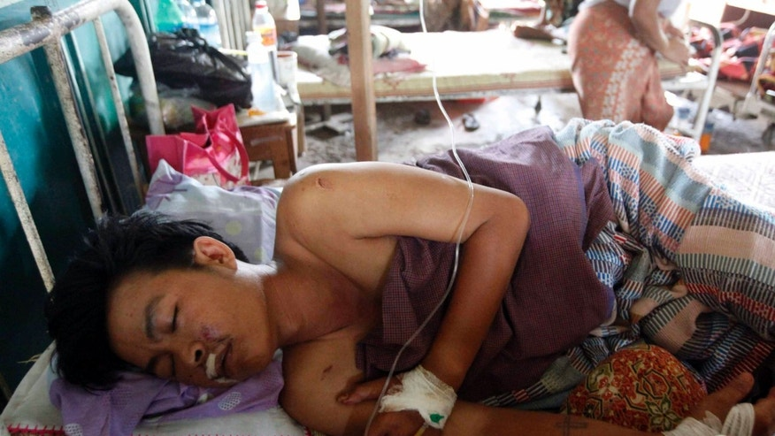 In this Wednesday, Oct. 2, 2013 photo, an injured Rakhine man receives medical treatment at Thandwe hospital in Thandwe, Rakhine State, western Myanmar. Terrified Muslim families hid in forests in western Myanmar on Wednesday, a day after fleeing new sectarian violence that erupted even as the president toured the divided region. Buddhist mobs killed a 94-year-old woman and four other Muslims and burned dozens of homes in unrest Tuesday near the coastal town of Thandwe. (AP Photo/Khin Maung Win)