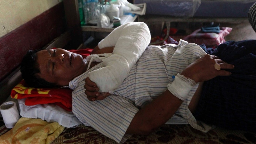 An injured Rakhine, Burma, man rests as he receives medical treatment at Thandwe hospital Wednesday, Oct. 2, 2013, in Thandwe, Rakhine State, western Myanmar.  Some terrified Muslim families have hidden in forests in western Myanmar from Buddhist mobs on Wednesday, fleeing from a new round of deadly sectarian violence in the region. (AP Photo/Khin Maung Win)