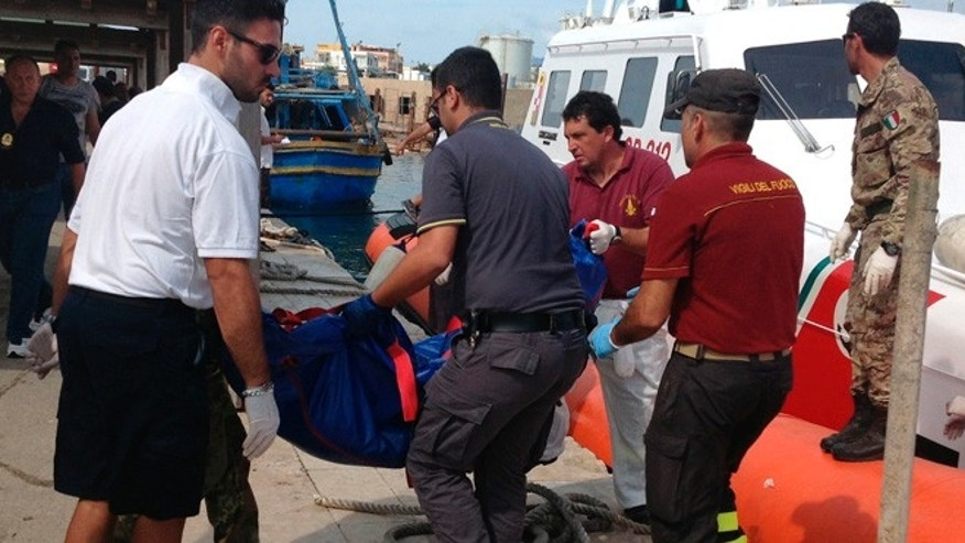 Oct. 3, 2013: Firefighters unload the body of a drowned migrant from a Coast Guard boat in the port of Lampedusa, Sicily.