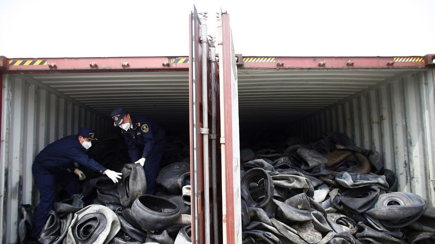 In this photo taken April 11, 2013, Chinese customs officials check a container of illegally imported used tires in Shanghai. China for years has welcomed the world's trash, creating a roaring business in recycling and livelihoods for tens of thousands. Now authorities are clamping down on an industry that has helped the rich West dispose of its waste but also added to the degradation of China's environment. (AP Photo) CHINA OUT