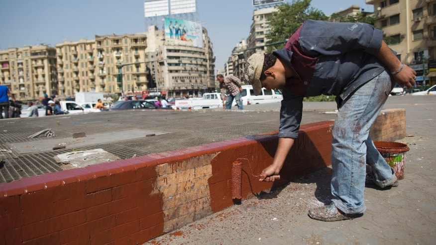 An Egyptian Municipality workers paints a sidewalk in Tahrir Square, Cairo, Egypt, Wednesday, Oct. 2, 2013. Egypt's army-backed interim government is sprucing up Cairo's famed Tahrir Square ahead of planned celebrations in honor of the military this weekend. Supporters of ousted President Mohammed Morsi are also planning counter-rallies in the square, the center for Egypt's recent uprisings against successive leaders, raising the specter of renewed violent confrontations. (AP Photo/Hassan Ammar)