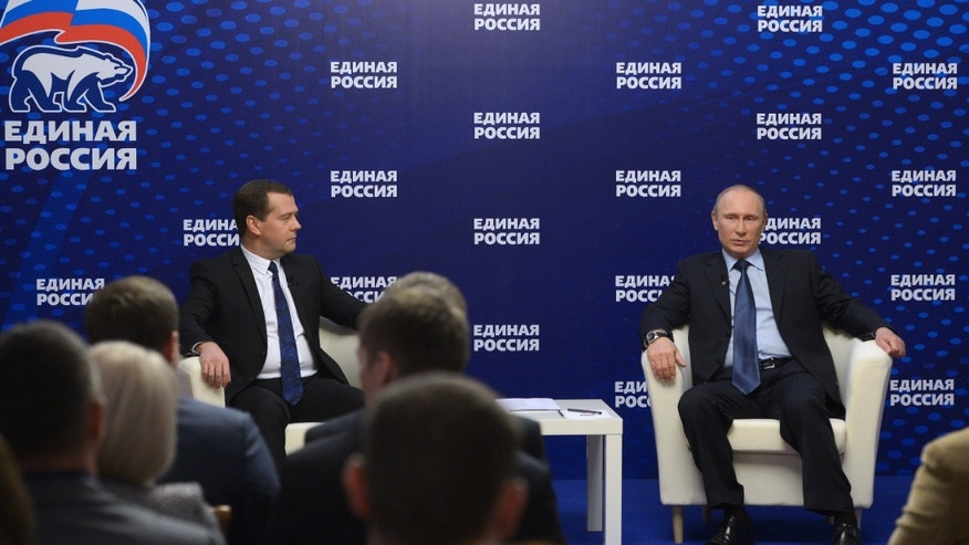 Russian President Vladimir Putin, right, and Prime Minister Dmitry Medvedev, left, meet with activists of the United Russia party outside Moscow, Russia, Thursday, Oct. 3, 2013. President Vladimir Putin says that Russia will expand its presence in the Arctic and restore a Soviet-era military base there. A sign reads The United Russia. At left is the party's emblem. (AP Photo/RIA-Novosti, Alexander Astafyev, Government Press Service)