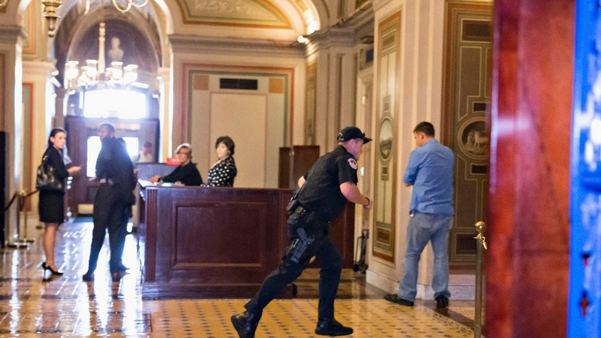 A Capitol Police officer runs through the first floor of the Senate on Capitol Hill during the lockdown order.