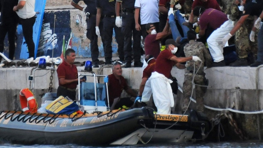 Rescuers lift a body as they reach the port of Lampedusa, southern Italy, Thursday, Oct. 3, 2013. At least 114 people died and scores more were missing late Thursday after a crowded fishing boat carrying African migrants from Tripoli caught fire, flipped over and sank, Italian officials said. Between 450 and 500 people were believed to be on board; health commissioner Antonio Candela said only 159 were rescued. (AP Photo/Danilo Taralli)