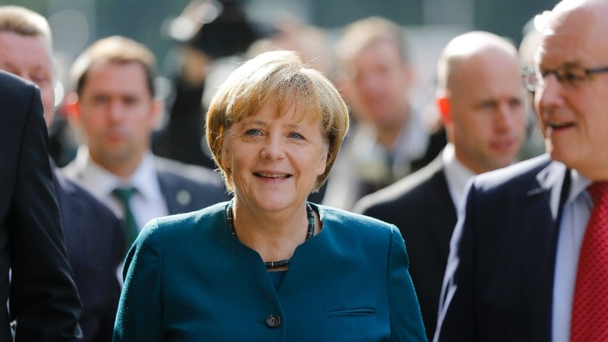 "German Chancellor Angela Merkel, center, chairwoman of the Christian Democratic party CDU arrives for preliminary talks after last month' election on forming Germany's next government, in Berlin, Friday, Oct. 4, 2013. The two parties CDU and CSU that make up the conservative Union bloc and the SPD are expected to discuss how much common ground there is to create a ""grand coalition"" like the one that governed Germany during Merkel's first term from 2005 to 2009. (AP Photo/Markus Schreiber)"
