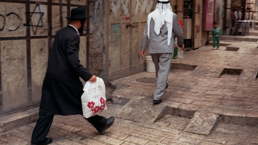 """FOR STORY ISRAEL NATION : In this June 12, 1997 file photo, an Orthodox man walks behind a Palestinian man on a street in the walled Old City of Jerusalem.  Israel's national population registry lists many """"nationalities"""" and ethnicities, among them Jew, Arab, Druze and more, but one ethnicity is conspicuously absent from the list: Israeli. The Israeli Supreme Court ruled this week that residents cannot identify themselves as Israelis in the national registry because it could affect the country's Jewish character, in court documents obtained Thursday, Oct, 3, 2013. (AP Photo/Greg Marinovich, File)"""