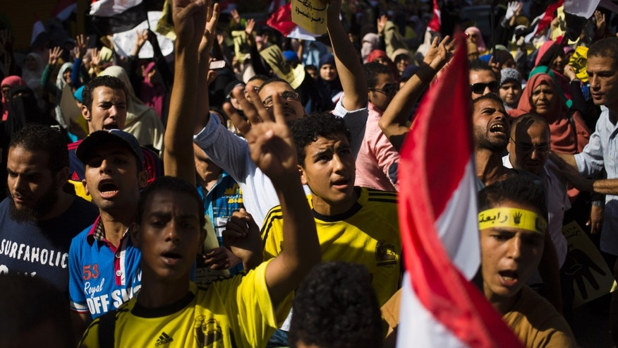 Oct. 4, 2013 - Supporters of Egypt's ousted President Mohammed Morsi chant slogans against Egyptian Defense Minister Gen. Abdel-Fattah el-Sissi and hold placards showing an open palm with four raised fingers, which has become a symbol of the Rabaah al-Adawiya mosque, where Morsi supporters had held a sit-in for weeks that was violently dispersed in August during a protest in Cairo.