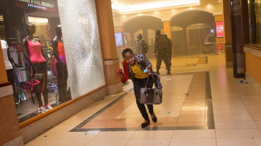 FILE - In this Saturday, Sept. 21, 2013 file photo, a woman who had been hiding during the gun battle runs for cover after armed police enter the Westgate Mall in Nairobi, Kenya, after gunmen threw grenades and opened fire. The Sept. 21 terrorist attack on Nairobi's Westgate Mall produced a raft of questions that haven't always had clear, complete answers and the answers to some questions have changed over time - The Associated Press attempts to define what is known and not known about the deadly mall attack. (AP Photo/Jonathan Kalan, File)