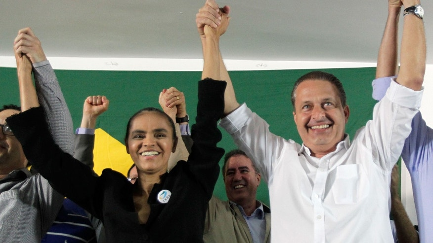 Marina Silva, left, a former senator and environment minister, and Pernambuco state Gov. Eduardo Campos, raise their arms as they celebrate her alliance with the Brazilian Socialist Party that will allow her to compete in the upcoming presidential election, in Brasilia, Brazil, Saturday, Oct. 5, 2013. Silva, the top-polling opposition candidate for next year's presidential election, had failed to obtain enough signatures to register her new party, Brazil's top electoral court ruled Thursday evening, keeping her from competing unless she signed on with another party. (AP Photo/Eraldo Peres)