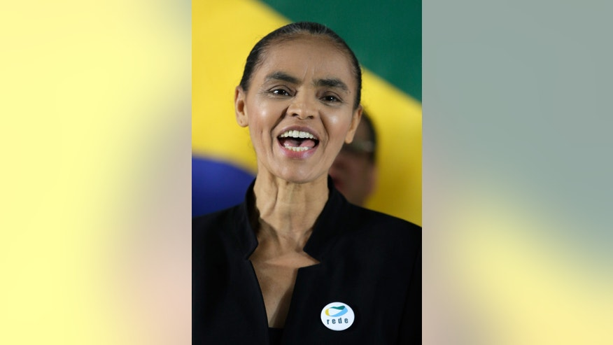 Marina Silva, left, a former senator and environment minister, sings her country's national anthem, during an event announcing her alliance with the Brazilian Socialist Party that will allow her to compete in the upcoming presidential election, in Brasilia, Brazil, Saturday, Oct. 5, 2013. Silva, the top-polling opposition candidate for next year's presidential election, had failed to obtain enough signatures to register her new party, Brazil's top electoral court ruled Thursday evening, keeping her from competing unless she signed on with another party. (AP Photo/Eraldo Peres)