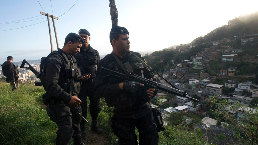 Police officers patrol the Lins slum complex during an operation to install a Pacifying Police Unit (UPP) in Rio de Janeiro on Sunday, Oct. 6, 2013. Elite police units backed by armored military vehicles and helicopters invaded the 12 communities part of the Lins slum complex. The action is part of a policing program aiming to drive violent and heavily armed drug gangs out of Rio's slums, where the traffickers have ruled for decades. (AP Photo/Silvia Izquierdo)