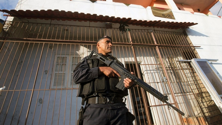 A police officer patrols the Lins slum complex during an operation to install a Pacifying Police Unit (UPP) in Rio de Janeiro on Sunday, Oct. 6, 2013. Elite police units backed by armored military vehicles and helicopters invaded the 12 communities part of the Lins slum complex. The action is part of a policing program aiming to drive violent and heavily armed drug gangs out of Rio's slums, where the traffickers have ruled for decades. (AP Photo/Silvia Izquierdo)