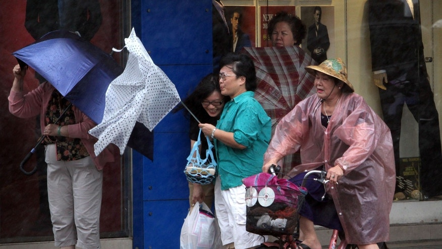 Taiwanese women hold their umbrellas against powerful gusts of wind as Typhoon Fitow approaches in Taipei, Taiwan, Sunday, Oct. 6, 2013. (AP Photo/Chiang Ying-ying)