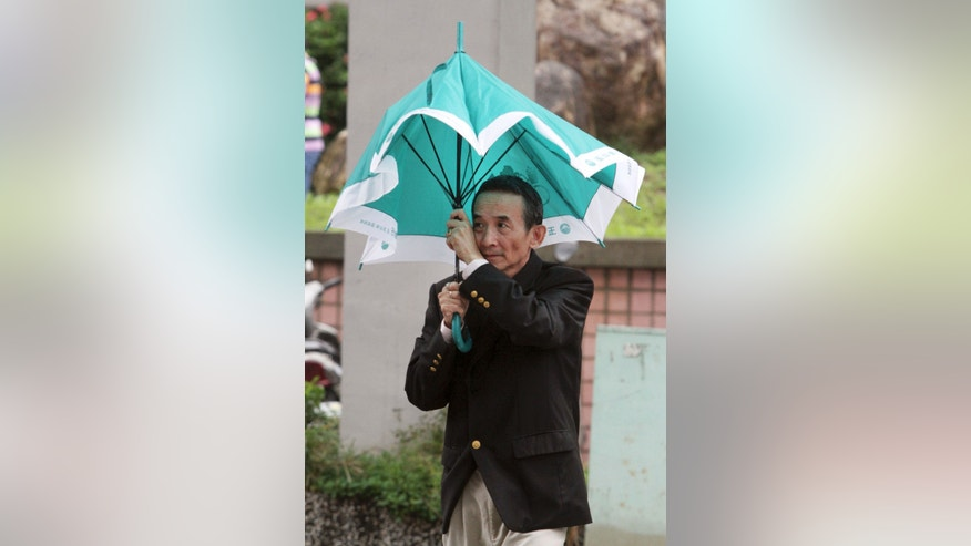 A Taiwanese man holds his umbrella against powerful gusts of wind as Typhoon Fitow approaches in Taipei, Taiwan, Sunday, Oct. 6, 2013. (AP Photo/Chiang Ying-ying)