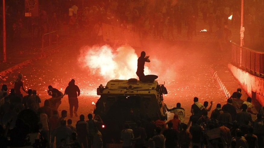 Oct. 6, 2013: A riot police officer, on a armored personnel carrier surrounded by anti-Morsi protesters (foreground), fires rubber bullets at members of the Muslim Brotherhood and supporters of ousted Egyptian President Mohammed Morsi along a road at Ramsis square, which leads to Tahrir Square, during clashes at a celebration marking Egypt's 1973 war with Israel, in Cairo. At least 28 people were killed and more than 90 wounded in clashes during protests in Egypt on Sunday, security sources and state media said, as the crisis since the army seized power three months ago showed no sign of abating.