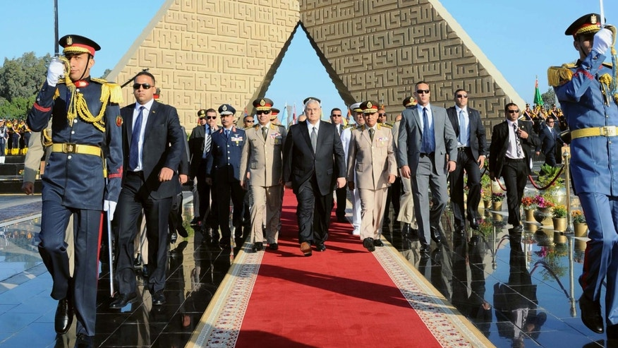 In this photo released by the Egyptian Presidency, Egypt's interim President Adly Mansour, center, Defense Minister Abdel-Fatah el-Sissi, center left, and other officials pay a visit to the Tomb of the Unknown Soldier and President Anwar Sadat's memorial as part of celebrations marking the 40th anniversary of the start of the 1973 Middle East war in which Egyptian forces made initial gains against Israel, Saturday, Oct. 5, 2013. Egypt's army is on high alert ahead of expected mass demonstrations by supporters of ousted Islamist President Mohammed Morsi timed to coincide with annual celebrations honoring the military, a combination many fear will lead to a new round of violence. (AP Photo/Egyptian Presidency)