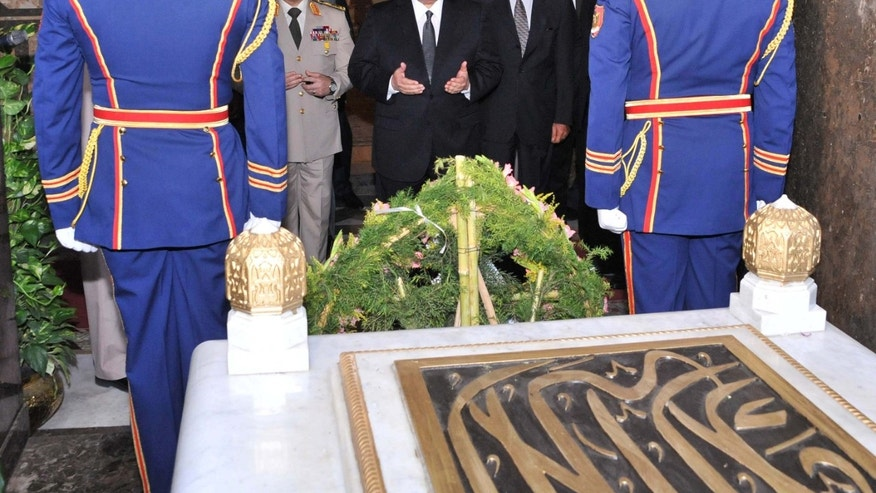 In this photo released by the Egyptian Presidency, Egypt's interim President Adly Mansour, center, Defense Minister Abdel-Fatah el-Sissi, center left, and other officials pray during a visit to the tomb of Egypt's charismatic leader Gamal Abdel-Nasser as part of celebrations marking the 40th anniversary of the start of the 1973 Middle East war in which Egyptian forces made initial gains against Israel, Saturday, Oct. 5, 2013. Egypt's army is on high alert ahead of expected mass demonstrations by supporters of ousted Islamist President Mohammed Morsi timed to coincide with annual celebrations honoring the military, a combination many fear will lead to a new round of violence. (AP Photo/Egyptian Presidency, File)