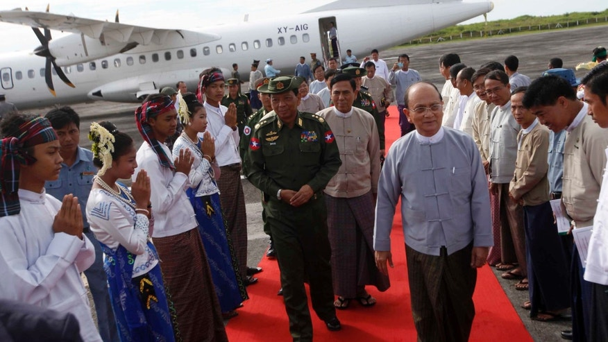 FILE -In this Oct. 2, 2013 file photo, Myanmar President Thein Sein,  front right, is welcomed by local residents upon his arrival at Thandwe airport in Thandwe, Rakhine State, western Myanmar. Even as the president came to western Myanmar to urge an end to sectarian violence, security forces could not prevent Buddhist mobs from torching the homes of minority Muslims or hacking them to death, at times, unwittingly, even encouraging them. That has raised questions about the government's ability to quench a virulent strain of religious hatred blamed for the deaths of more than 240 people in the last 18 months. The latest attack occurred Tuesday, Oct. 1, in Thandwe township, killing five just hours before President Thein touched down for a scheduled visit. (AP Photo/Khin Maung Win, File)