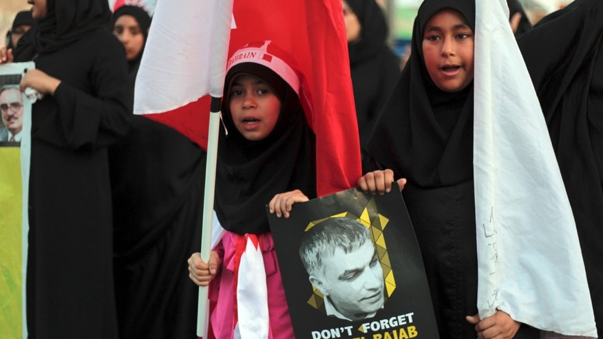 "Young Bahraini anti-government protesters carry national flags and a poster of jailed human rights activist Nabeel Rajab with words in Arabic reading, ""so we don't forget,"" during a march in the western village of Malkiya, Bahrain, Thursday, Oct. 3, 2013. People marched to protest against jail terms handed down in the past week to rights activists and protesters, including four people sentenced to life in prison for a bombing that authorities said targeted police in the Gulf nation. (AP Photo/Hasan Jamali)"