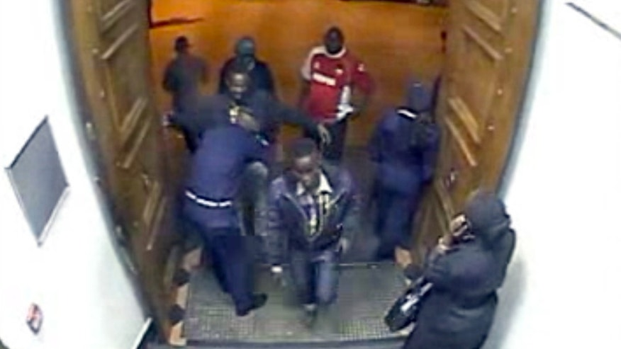 In this image from closed circuit television footage released by Kenya's counterterrorism police Sunday, Oct. 6, 2013, two men, one believed to be Adan Dheq, also known as Hussen Abdi Ali, center, and the other, believed to be Abd Kadir Haret Muhamed, also known as Mohamed Hussen, being searched by a guard at left, enter a Barclays Bank branch in Nairobi, Kenya. The men withdrew enough money to pay for a Mitsubishi Lancer car that police say was used to bring the terrorists to the Westgate Mall, indicating the deadly attack was planned weeks in advance, officials said. (AP Photo/APTN)
