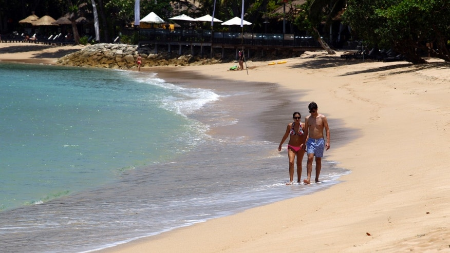 Foreign tourists stroll along a beach in Bali, Indonesia, Monday, Oct. 7, 2013. A decade ago, Bali's famed white sand beaches and popular shopping areas were deserted after suicide bombings that killed 202 mostly foreign tourists in 2002. But the Hindu-dominated resort island has worked to overcome that image and is sending a message to the world this week that it's now on a Bali high by hosting leaders and more than 8,000 delegates, business people and journalists at the 21-member Asia-Pacific Economic Cooperation summit. (AP Photo/Firdia Lisnawati)