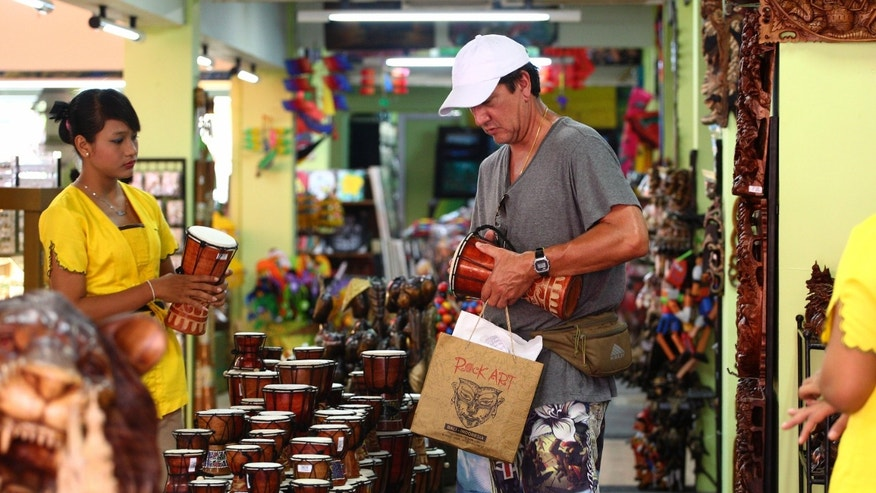 A foreign tourist looks at souvenirs at a shop in Bali, Indonesia, Monday, Oct. 7, 2013. The dark cloud of the suicide bombings that killed 202 mostly foreign tourists in 2002 lingered for years, decimating one of Asia's top tourist destinations. But the Hindu-dominated resort island has worked to overcome that image and is sending a message to the world this week that it's now on a Bali high by hosting leaders and more than 8,000 delegates, business people and journalists at the 21-member Asia-Pacific Economic Cooperation summit. (AP Photo/Firdia Lisnawati)
