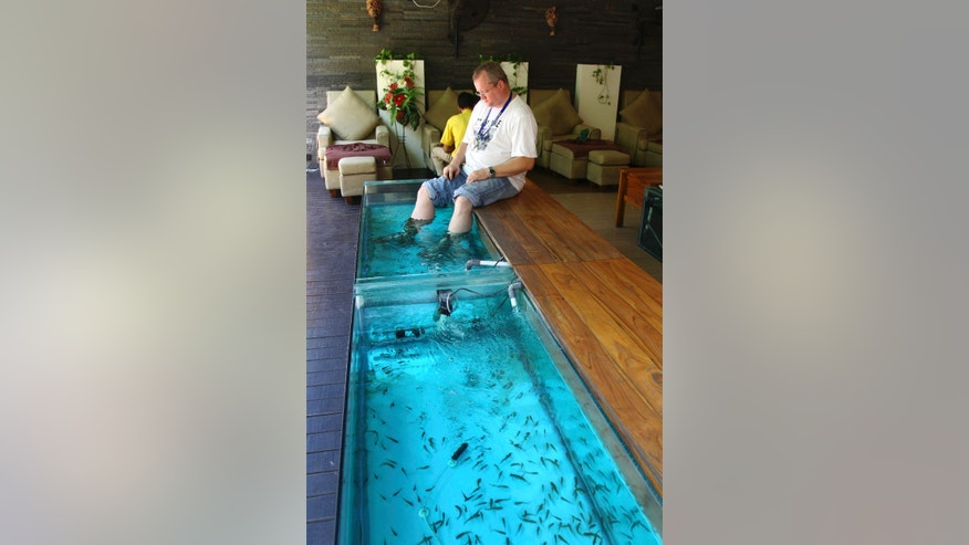 "A foreign tourist dips his feet into a fish tank at a fish spa salon in Bali, Indonesia, Monday, Oct. 7, 2013. A decade ago, Bali's famed white sand beaches and popular shopping areas were deserted after suicide bombings that killed 202 mostly foreign tourists in 2002. But the Hindu-dominated resort island has worked to overcome that image and last year nearly 3 million visited the island, which was also boosted after Julia Roberts filmed on location for the movie ""Eat, Pray, Love."" (AP Photo/Firdia Lisnawati)"