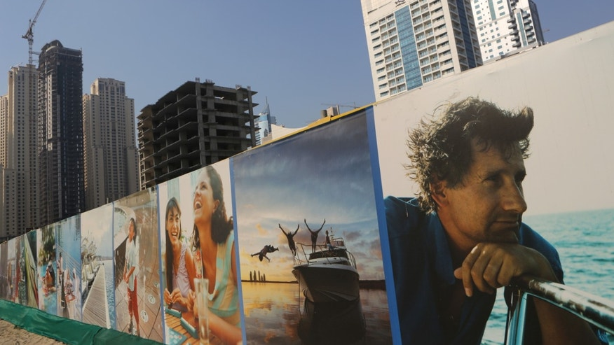 A panoramic advertising billboard is set up by an unfinished building, center, which has been left the same since the 2009 financial crisis in Dubai, United Arab Emirates, Tuesday, Oct. 8, 2013. A hunger strike started in September by a few prisoners, convicted under the strict financial codes of the United Arab Emirates, has now grown to more than 50 people demanding authorities reconsider their sentences that can bring years behind bars for a single bounced check. (AP Photo/Kamran Jebreili)