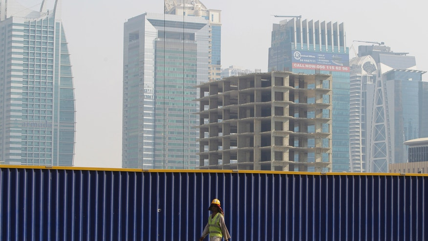 A laborer passes by an unfinished construction tower which has been left the same since the 2009 financial crisis in Dubai, United Arab Emirates, Tuesday, Oct. 8, 2013. A hunger strike started in September by a few prisoners, convicted under the strict financial codes of the United Arab Emirates, has now grown to more than 50 people demanding authorities reconsider their sentences that can bring years behind bars for a single bounced check. (AP Photo/Kamran Jebreili)